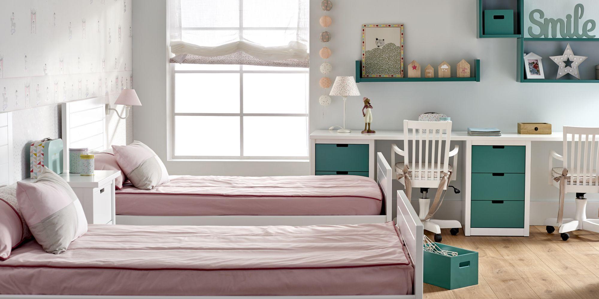 Habitación juvenil con 2 camas separadas y mesa de estudio con cajones